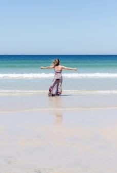Mujer relajante en la playa con los brazos abiertos disfrutando de su libertad