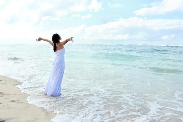 Mujer relajante en la playa con los brazos abiertos