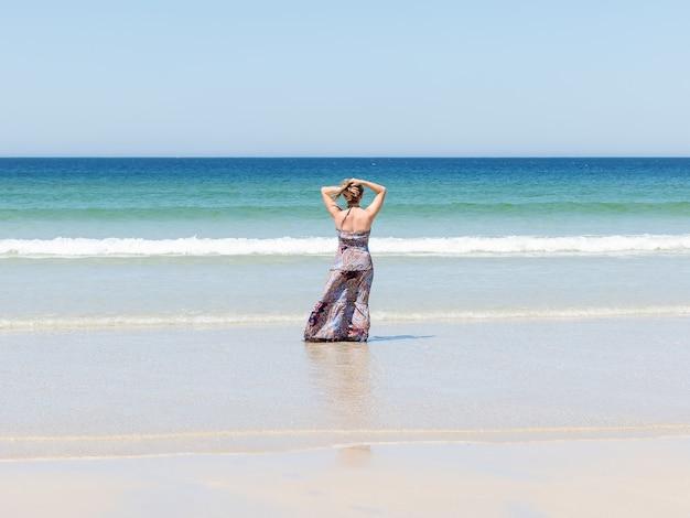 Mujer relajante en la playa disfrutando de su libertad