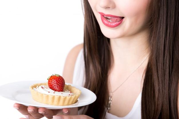 Mujer relamiéndose con un pastel