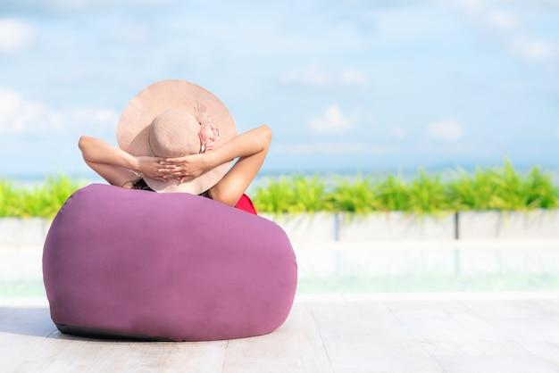 Mujer relexing en beanbag por la piscina en verano