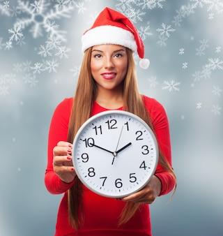Mujer con un reloj grande en un fondo de copos de nieve