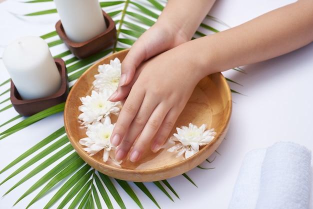 Mujer remojando sus manos en un recipiente con agua y flores, tratamiento de spa y producto para pies femeninos y spa de manos, masaje de guijarros, agua de flores perfumadas y velas, relajación. endecha plana. vista superior.