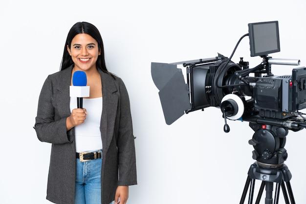 Mujer reportera colombiana sosteniendo un micrófono y reportando noticias en la pared blanca manteniendo los brazos cruzados en posición frontal