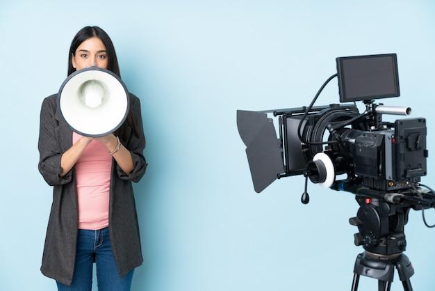 Mujer reportera sosteniendo un micrófono y reportando noticias aisladas en la pared azul gritando a través de un megáfono