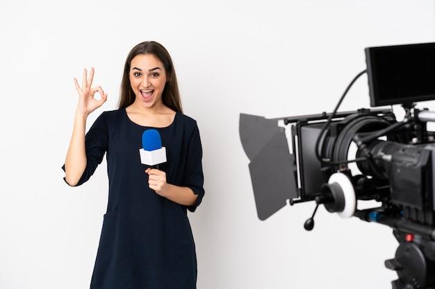 Mujer reportera sosteniendo un micrófono y reportando noticias en blanco sorprendido y mostrando signo ok
