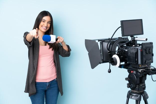 Mujer reportera sosteniendo un micrófono y reportando noticias en puntos azules dedo mientras sonríe