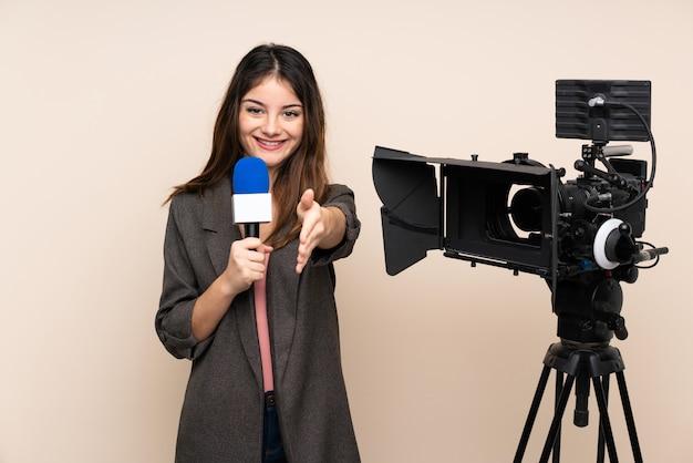 Mujer reportera sosteniendo un micrófono y reportando noticias sobre el apretón de manos de la pared después de un buen trato