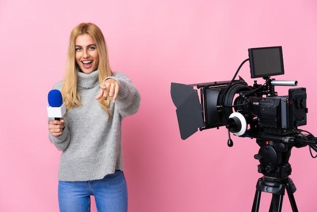 Mujer reportera sosteniendo un micrófono y reportando noticias sobre frente señalador rosa aislado con expresión feliz