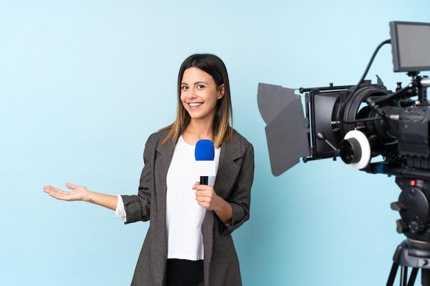 Mujer reportera sosteniendo un micrófono y reportando noticias sobre pared azul aislada con copyspace imaginario en la palma