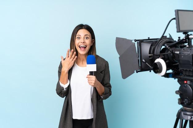 Mujer reportera sosteniendo un micrófono y reportando noticias sobre una pared azul aislada con expresión facial sorpresa