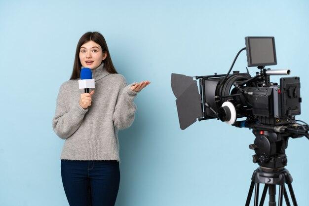 Mujer reportera sosteniendo un micrófono y reportando noticias sobre pared azul