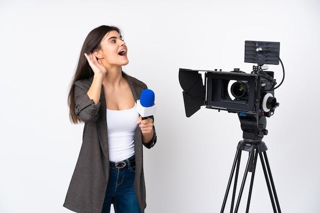 Mujer reportera sosteniendo un micrófono y reportando noticias sobre una pared blanca aislada escuchando algo