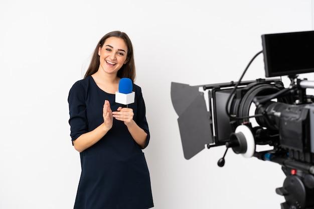 Mujer reportera sosteniendo un micrófono y reportando noticias sobre una pared blanca aplaudiendo después de la presentación en una conferencia