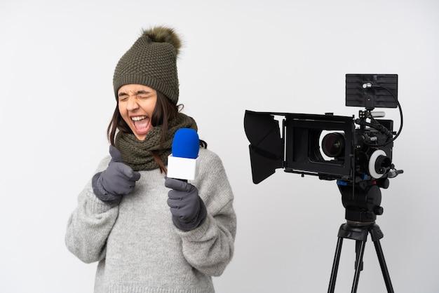 Mujer reportera sosteniendo un micrófono y reportando noticias sobre una pared blanca apuntando hacia el frente y sonriendo