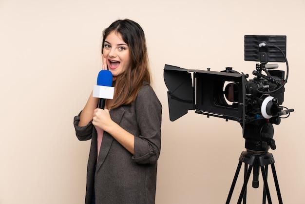 Mujer reportera sosteniendo un micrófono y reportando noticias sobre la pared con expresión facial sorprendida