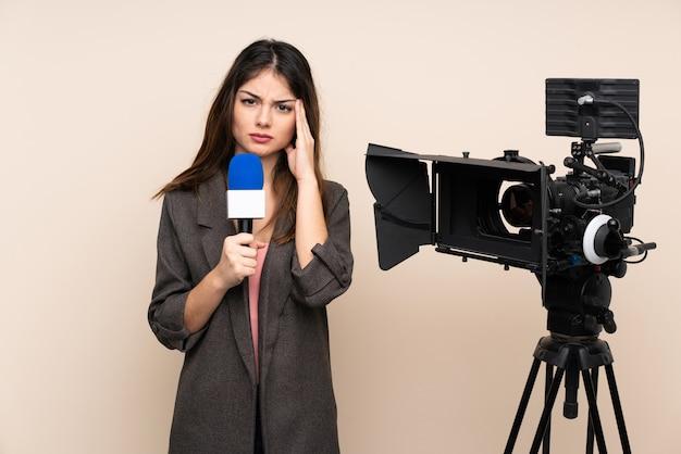 Mujer reportera sosteniendo un micrófono y reportando noticias sobre la pared infeliz y frustrada con algo