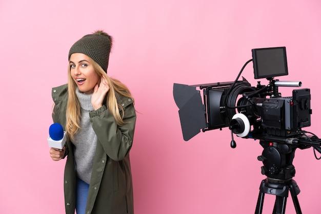 Mujer reportera sosteniendo un micrófono y reportando noticias sobre una pared rosa aislada escuchando algo poniendo la mano en la oreja