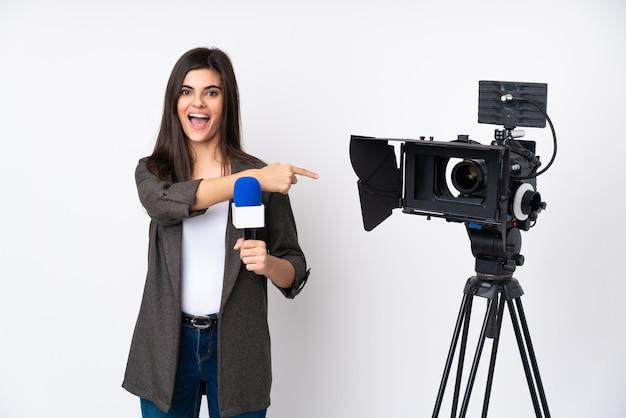 Mujer reportera sosteniendo un micrófono y reportando noticias sorprendidas y señalando con el dedo a un lado