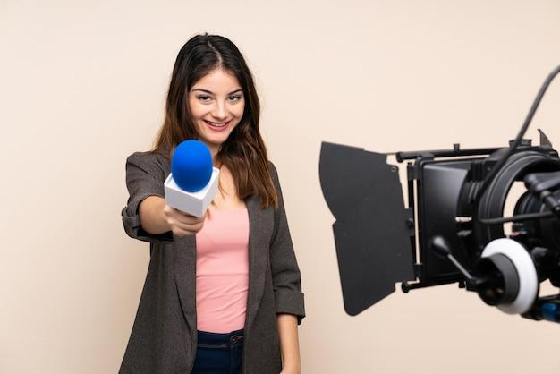 Mujer reportera sosteniendo un micrófono y reportando noticias