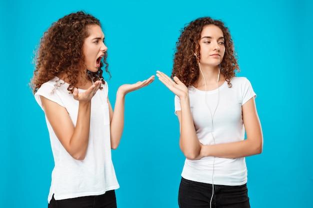 Mujer resentida con su hermana gemela en auriculares sobre azul.