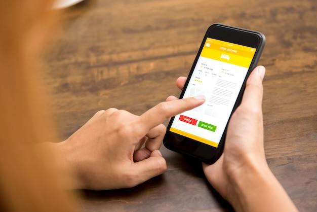 Mujer reserva hotel online por aplicación de teléfono móvil.