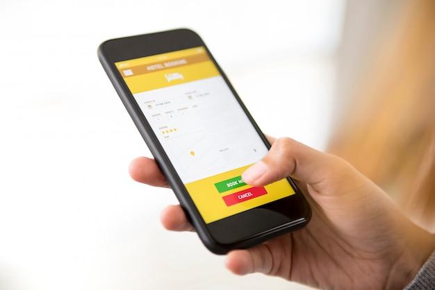 Mujer reservando hotel en línea a través de la aplicación de teléfono inteligente