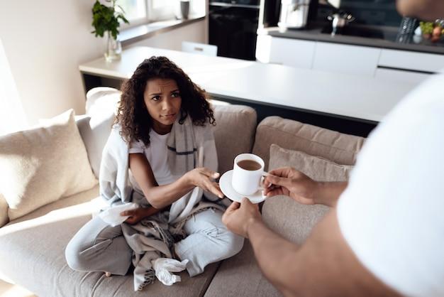 La mujer está resfriada y el hombre le trajo té caliente.
