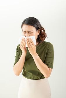 Mujer con un resfriado que sopla su nariz que moquea con un pañuelo