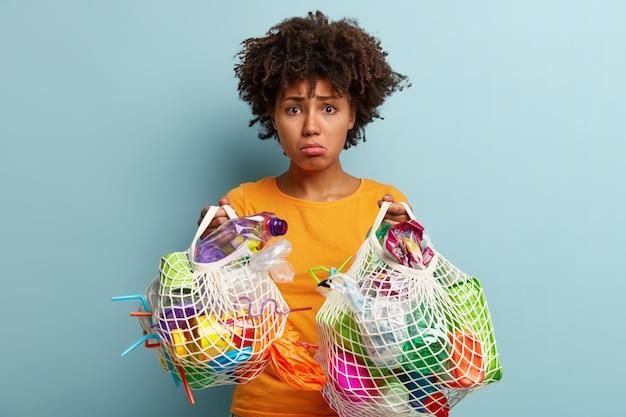 Mujer con residuos plásticos en bolsa de red