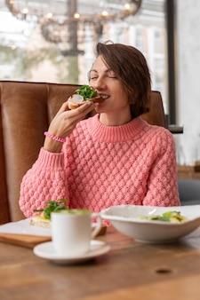 Mujer en un restaurante en un acogedor suéter caliente comiendo tostadas de desayuno saludable con rúcula y salmón