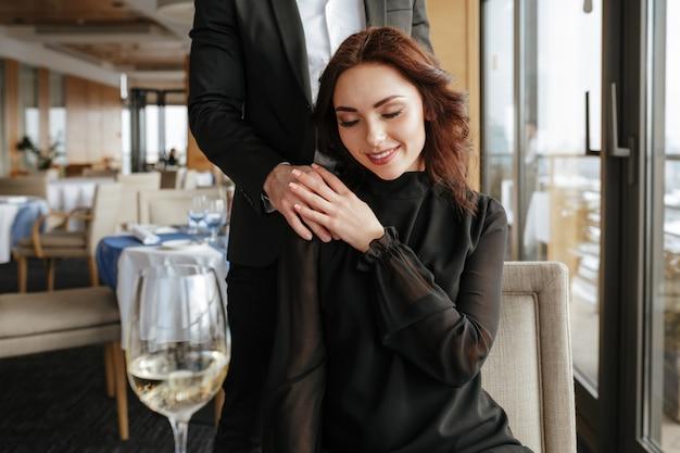 Mujer en restaurante con hombre detrás de ella