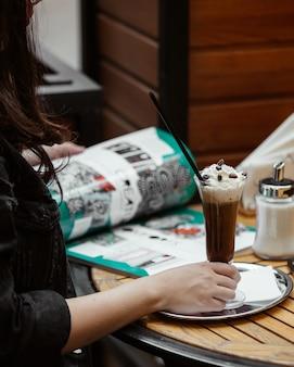 Mujer en un restaurante con revista y una copa de capuchino con crema.