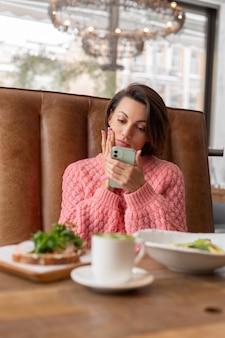 Una mujer en un restaurante con un suéter caliente está mirando algo en el teléfono, un delicioso desayuno saludable y un café con leche matcha en la mesa