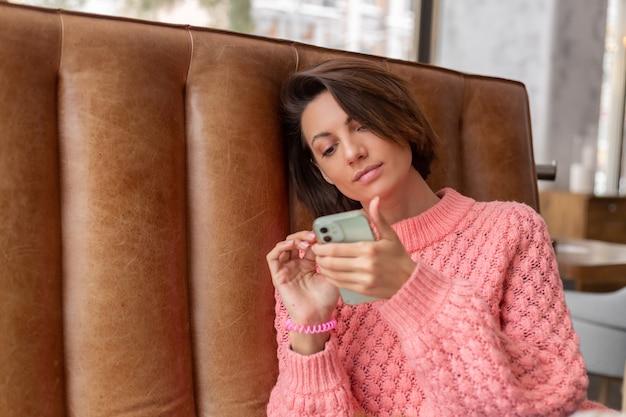 Mujer en un restaurante con un suéter caliente está mirando algo en el teléfono