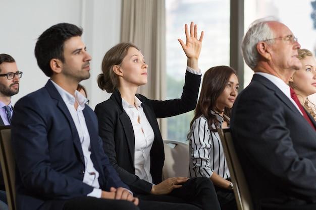 Mujer en una reunión con la mano levantada