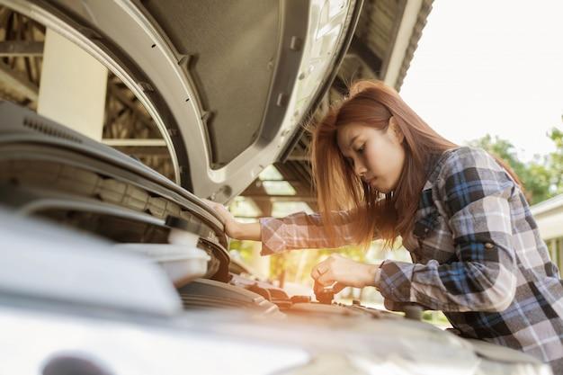 Mujer revisando un auto, cambiar el auto de aceite