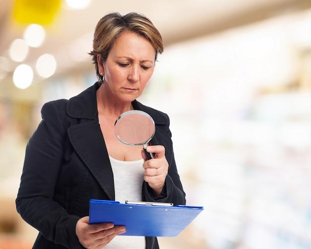 Mujer revisando una carpeta con una lupa
