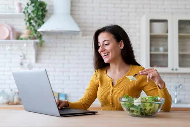 Mujer revisando laptop y comiendo ensalada