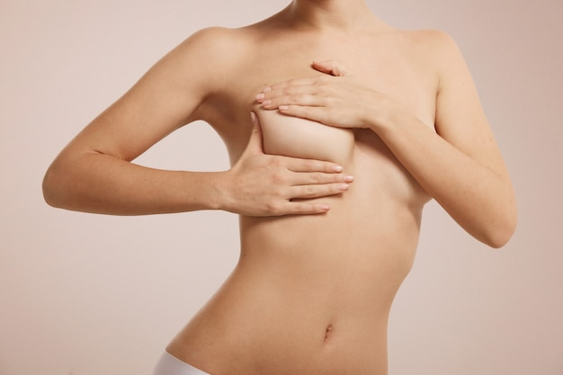 Mujer revisando su mama para detectar cáncer de mama