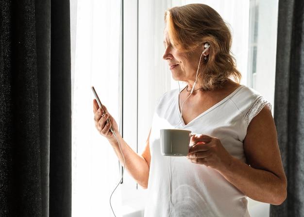 Mujer revisando su teléfono en casa mientras el distanciamiento social
