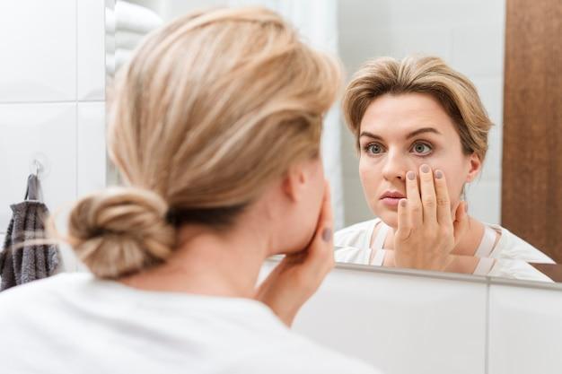 Mujer revisando sus ojos en el espejo