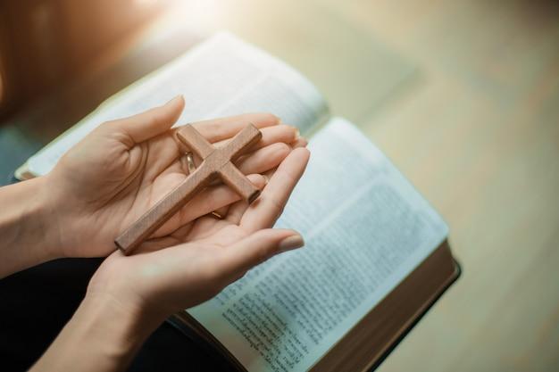 Mujer reza con biblia y cruz de madera.
