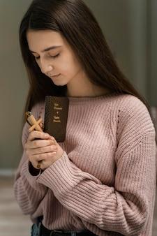Mujer rezando con cruz de madera y biblia