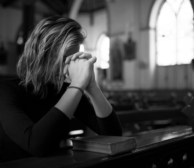 Mujer rezando en la iglesia en escala de grises