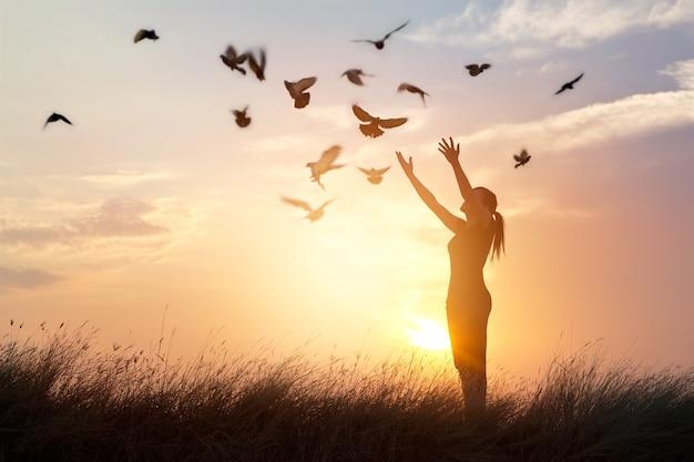 Mujer rezando y liberando a las aves a la naturaleza en el fondo del atardecer