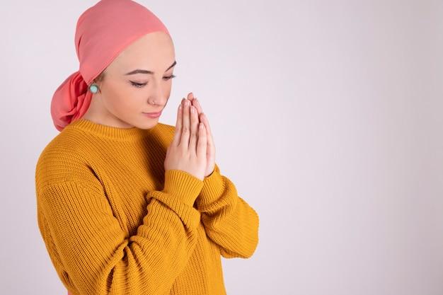 Mujer rezando luchando contra el cáncer