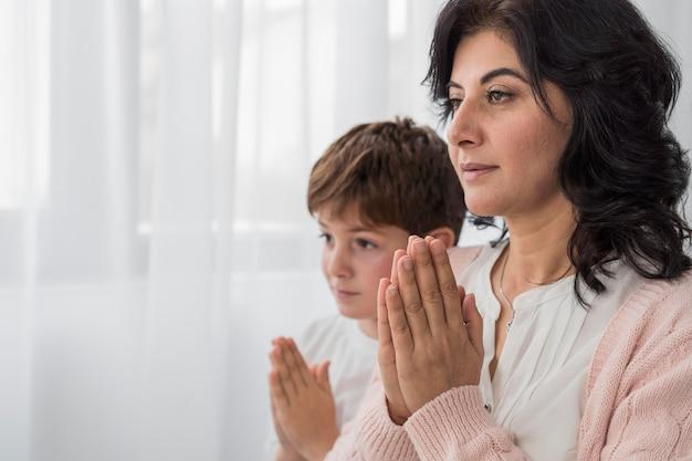 Mujer rezando con su hijo y copie el espacio