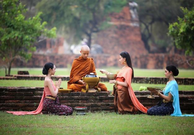Mujer rezar al monje con comida al aire libre