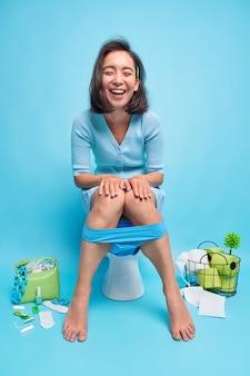 La mujer se ríe alegremente posa en la taza del inodoro revela que está de buen humor posa en el baño con diferentes artículos en azul estando en casa